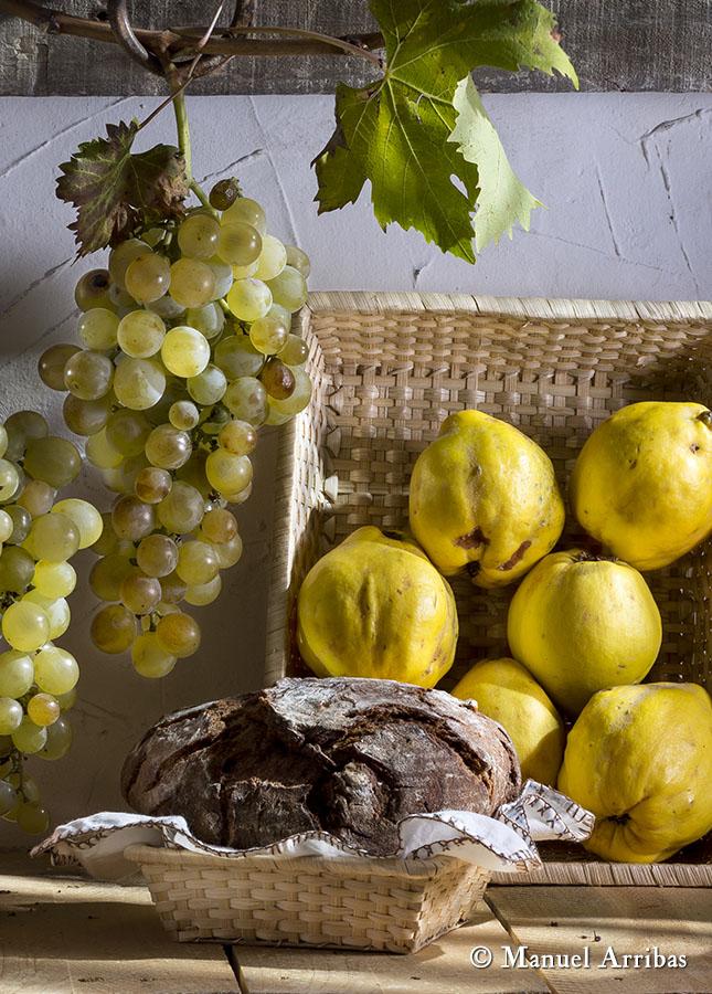 Bodegón con pan, limones y uvas. Fotografía de producto